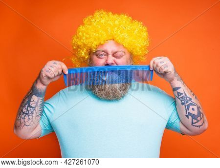 Fat Doubter Man With Beard, Tattoos And Sunglasses Combs Himself With A Giant Comb