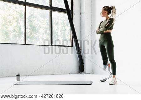 Young sportswoman with prosthesis standing while working out indoors
