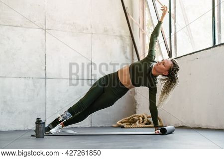 Young sportswoman with prosthesis doing exercise during yoga practice indoors