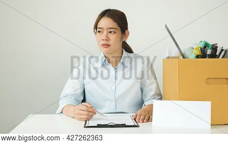 A Female Office Worker, Dissatisfied With The Termination, Packs Her Belongings In A Cardboard Box A