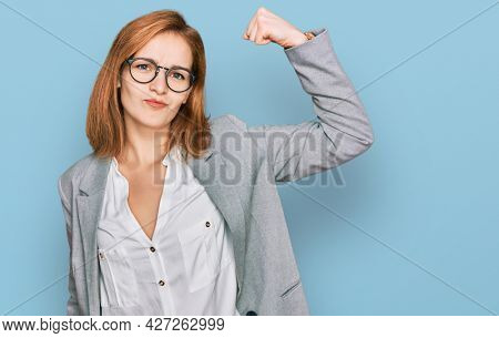 Young caucasian woman wearing business style and glasses strong person showing arm muscle, confident and proud of power
