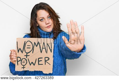 Young plus size woman holding woman power banner with open hand doing stop sign with serious and confident expression, defense gesture