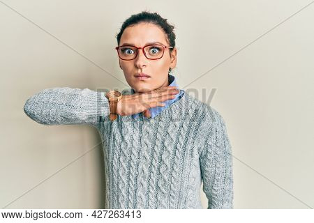 Young caucasian woman wearing casual clothes and glasses cutting throat with hand as knife, threaten aggression with furious violence