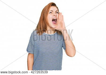 Young caucasian woman wearing casual clothes shouting and screaming loud to side with hand on mouth. communication concept.