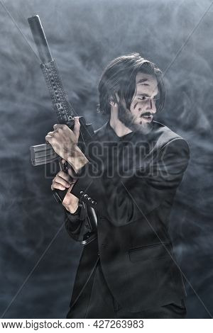 Dangerous gangster with automatic gun in his hands in the night on smoky background. Bad guy.