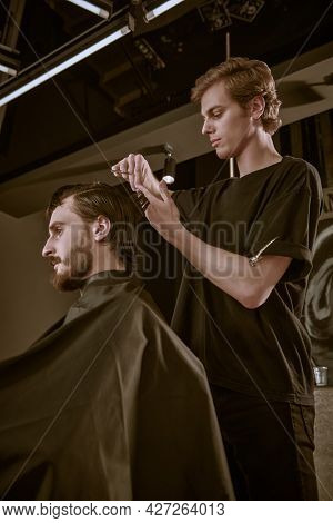 Making haircut look perfect. Handsome brunet man visiting hairstylist in barbershop.