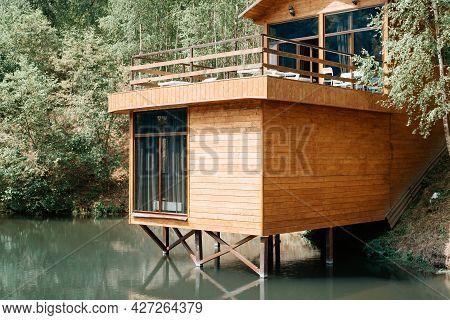 Modern Wooden Loft House On The Lake, Close-up. Exterior Of A Country House With A Balcony, Cottage