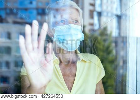Elderly Caucasian Women Wearing Protective Face Mask, In Home, Looking Outside Window. Old Lady Sadn