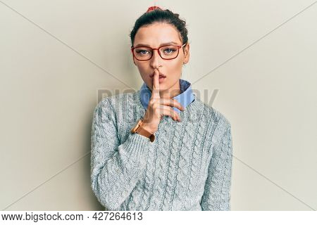 Young caucasian woman wearing casual clothes and glasses asking to be quiet with finger on lips. silence and secret concept.