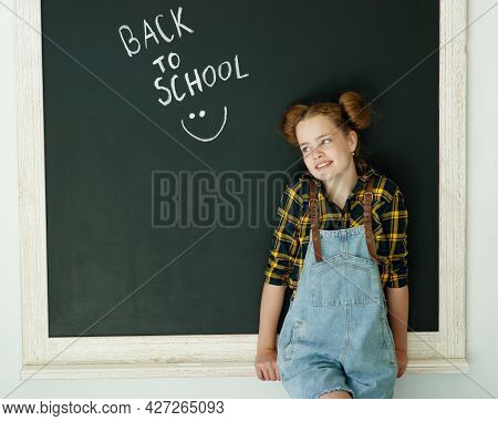 Happy Smiling Girl. Child At The Blackboard. Girl Indoor Classroom With Chalkboard On Background. We