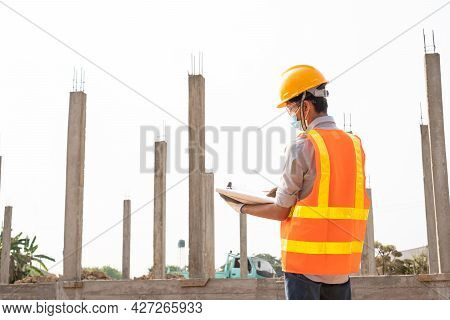 The Construction Site Male Engineer Or Architect Is Exploring And Inspecting The Outdoor Constructio