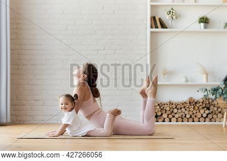 Cute Little Girl Looks At The Camera And Smiles, Repeating Her Body Flexibility Exercises After Her