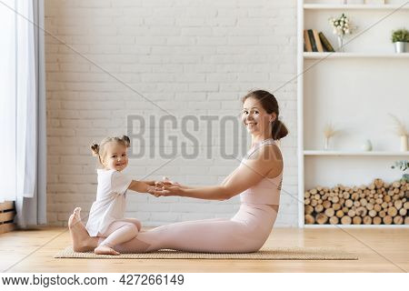 Beautiful Young Woman And Her Charming Little Daughter Are Smiling While Doing Yoga Together At Home