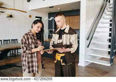 Young woman signing document held by plumber or repairman
