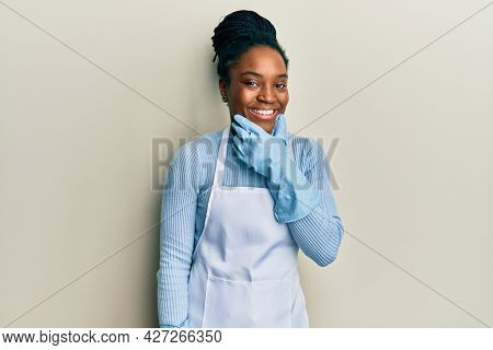 African american woman with braided hair wearing cleaner apron and gloves looking confident at the camera smiling with crossed arms and hand raised on chin. thinking positive.