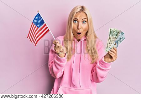 Young blonde woman holding united states flag and dollars afraid and shocked with surprise and amazed expression, fear and excited face.