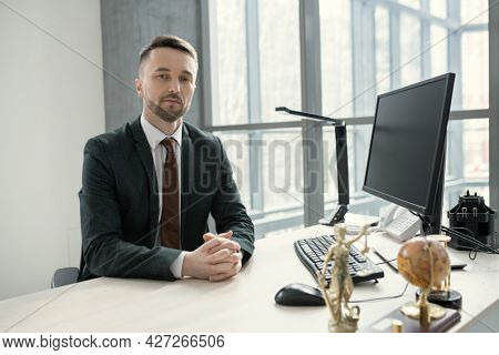 Portrait of young businessman in suit looking at camera while sitting at his workplace with computer on it