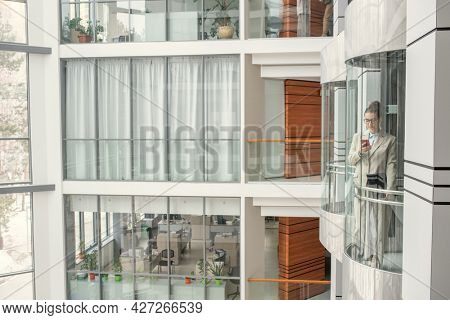 Image of modern office building with businesswoman using mobile phone while standing in elevator and going up