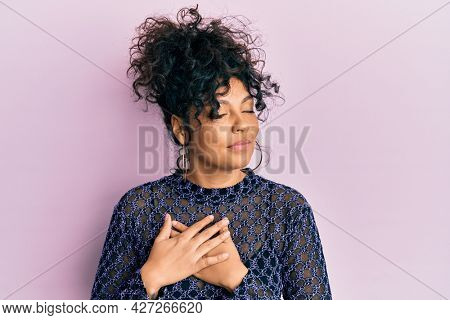 Young hispanic woman wearing casual clothes smiling with hands on chest, eyes closed with grateful gesture on face. health concept.
