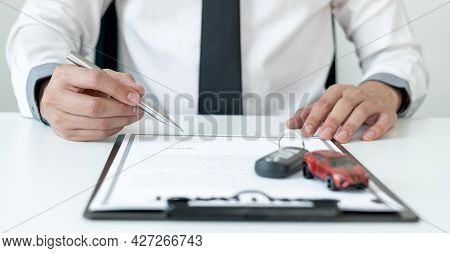 Car Dealer Businessman Signing Car Insurance Document Or Lease Paper. Car Loan And Insurance Concept