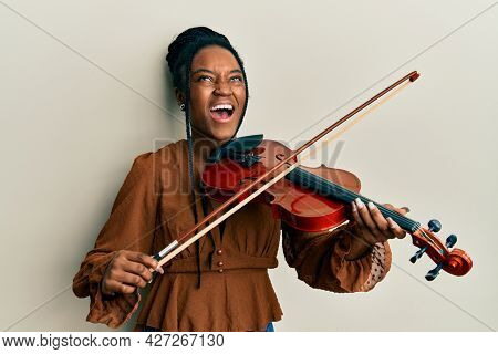 African american woman with braided hair playing violin angry and mad screaming frustrated and furious, shouting with anger looking up.