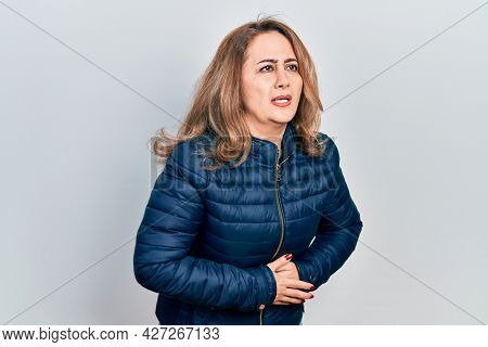 Middle age caucasian woman wearing casual clothes with hand on stomach because indigestion, painful illness feeling unwell. ache concept.