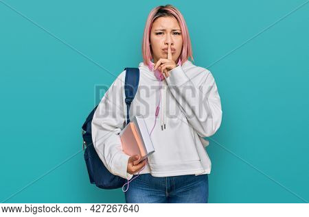 Hispanic woman with pink hair wearing student backpack and headphones asking to be quiet with finger on lips. silence and secret concept.