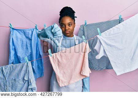African american woman with braided hair washing clothes at clothesline looking unhappy and angry showing rejection and negative with thumbs down gesture. bad expression.