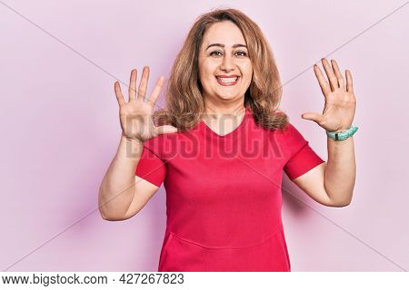 Middle age caucasian woman wearing casual clothes showing and pointing up with fingers number ten while smiling confident and happy.
