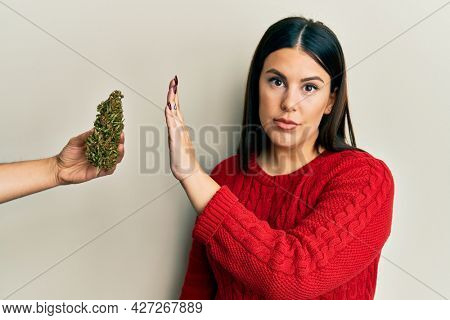 Beautiful brunette woman saying no to marijuana herb relaxed with serious expression on face. simple and natural looking at the camera.