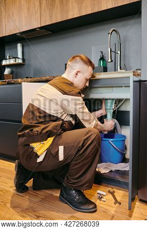 Modern plumber in workwear changing pipe under sink in the kitchen