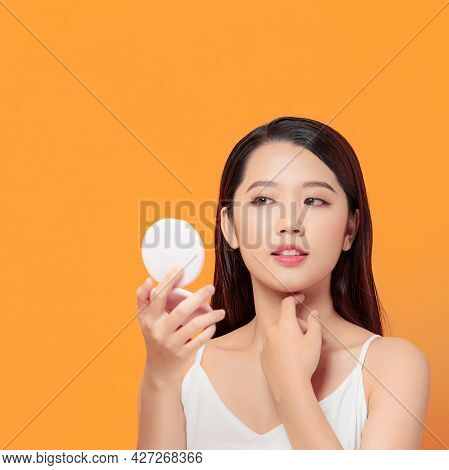 Young Pretty Woman Correcting Makeup Using Small Mirror
