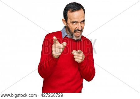 Middle age hispanic man wearing casual clothes pointing fingers to camera with happy and funny face. good energy and vibes.