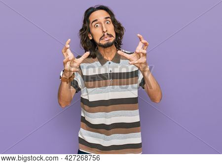 Young hispanic man wearing casual clothes shouting frustrated with rage, hands trying to strangle, yelling mad