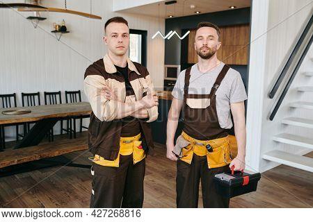 Two plumbers or repairmen in workwear standing in large domestic room