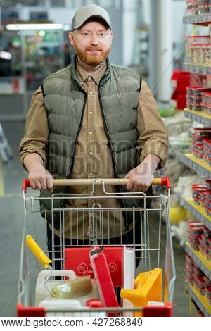 Male customer pushing cart with chosen household goods