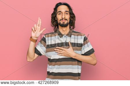 Young hispanic man wearing casual clothes smiling swearing with hand on chest and fingers up, making a loyalty promise oath