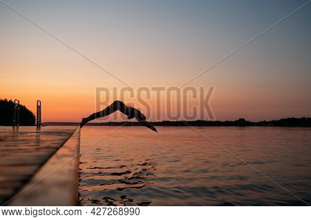 Woman Jumping Into The Lake From Wooden Pier. Having Fun On Summer Day On The Vacations. Young Girl
