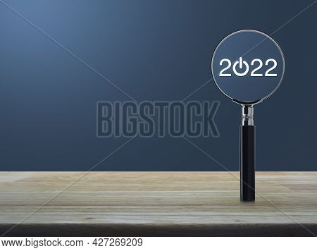2022 Start Up Flat Icon With Magnifying Glass On Wooden Table Over Light Blue Gradient Background, B