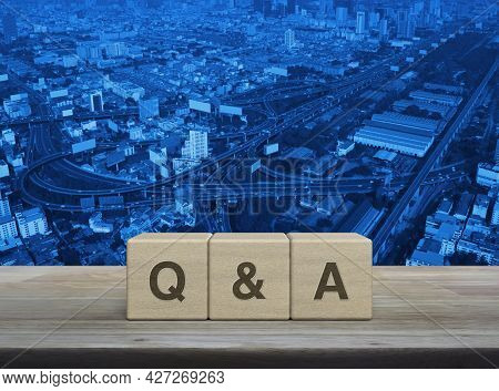 Q And A Letter On Block Cubes On Wooden Table Over Modern City Tower, Street, Expressway And Skyscra