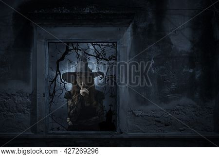 Halloween Witch Showing Silence Sign With Finger Over Lips Standing In Old Damaged Window With Wall