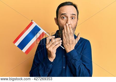 Middle age hispanic man holding philippines flag covering mouth with hand, shocked and afraid for mistake. surprised expression