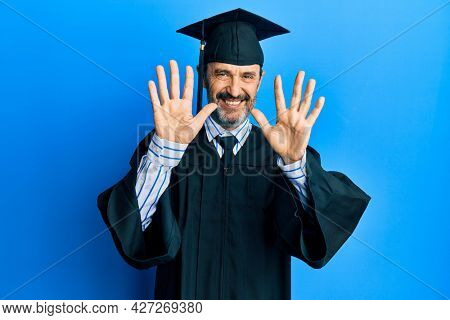 Middle age hispanic man wearing graduation cap and ceremony robe showing and pointing up with fingers number ten while smiling confident and happy.
