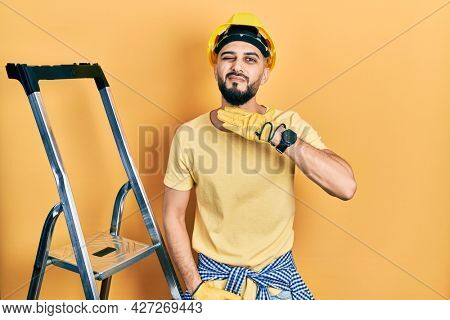 Handsome man with beard by construction stairs wearing hardhat cutting throat with hand as knife, threaten aggression with furious violence