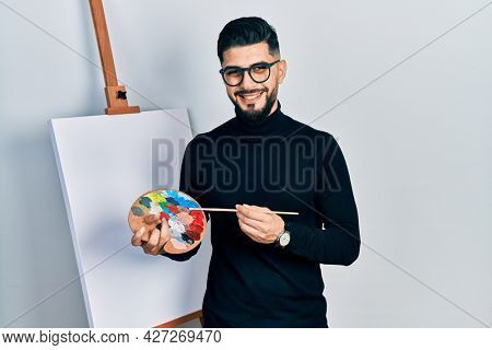 Handsome man with beard holding palette and brush close to easel stand smiling and laughing hard out loud because funny crazy joke.