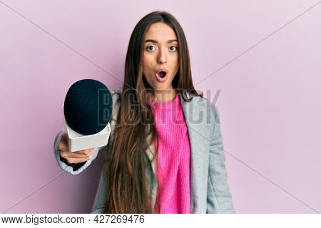 Young hispanic girl holding reporter microphone scared and amazed with open mouth for surprise, disbelief face