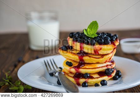 Pancakes With Corn Flour, Blueberries And Berry Jam On A White Plate On A Brown Wooden Background. P