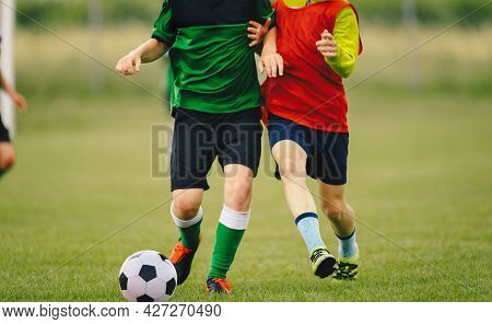 Two Soccer Players In A Duel On Grass Venue. Boys Running After Black And White Soccer Ball. Kids In