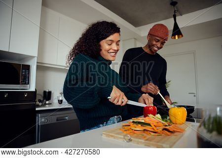 Young Mixed Race Couple Cooking Food In The Kitchen At Home. Happy Couple Preparing Food And Smiling