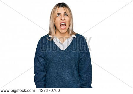 Young caucasian woman wearing casual clothes angry and mad screaming frustrated and furious, shouting with anger. rage and aggressive concept.